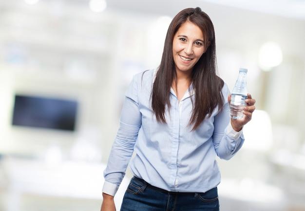Mulher de sorriso com uma garrafa de água
