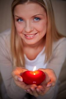 Mulher de sorriso com uma vela em forma de coração