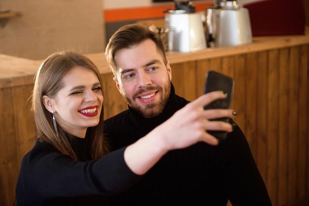 Mulher de sorriso e homem considerável que bebem o café, usando o telefone celular ao passar o tempo em uma cafetaria.