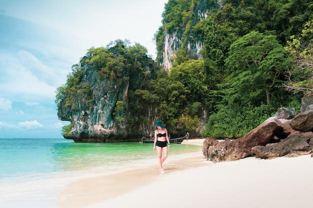 Mulher de sorriso feliz no biquini e no sunhat que andam na praia do mar.