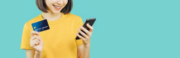 Mulher de sorriso feliz que guarda o cartão esperto do telefone e de crédito com compra em linha.