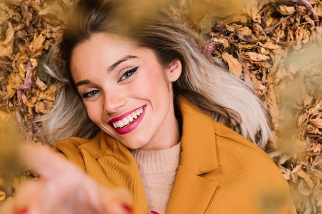 Mulher de sorriso moderna que olha a câmera que encontra-se nas folhas secas durante a estação do outono