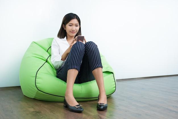 Mulher de sorriso no saco de feijão usando o telefone móvel