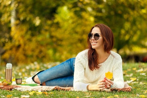 Mulher de sorriso no sweather branco feito malha e óculos de sol pretos que colocam na grama no parque do outono. ela segura uma folha amarela na mão.