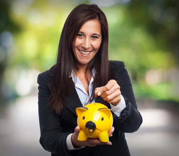 Mulher de sorriso no terno e atirar uma moeda em um banco piggy