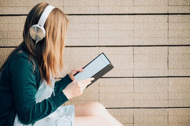Mulher de sorriso nos monóculos que lê o livro e que escuta a música com os fones de ouvido no parque exterior contra a luz solar, conceito do estilo de vida da cidade.