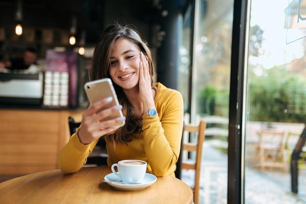 Mulher de sorriso nova que usa o smarphone no café. vista frontal.