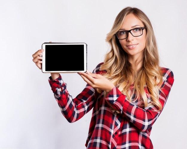 Mulher de sorriso ocasional que mostra a tela de tablet pc vazia sobre o fundo cinzento.