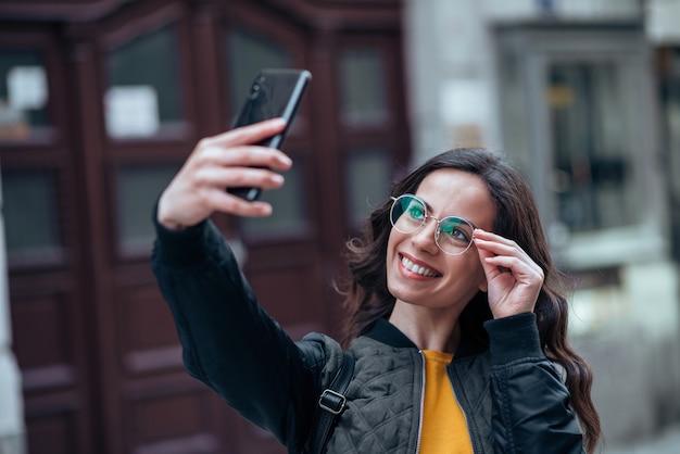 Mulher de sorriso ocasional que toma o selfie no telefone esperto na rua da cidade, close-up.