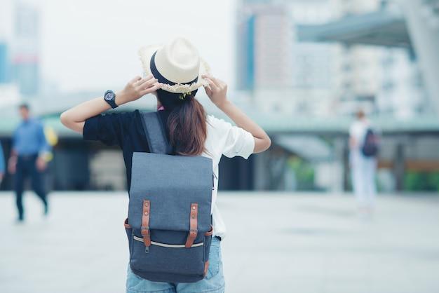 Mulher de sorriso que anda fora, jovem senhora que admira a vista da cidade com passagem e construções no fundo.