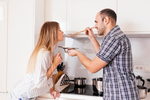 Mulher de sorriso que deixa o homem provar uma sopa com uma colher de madeira na cozinha