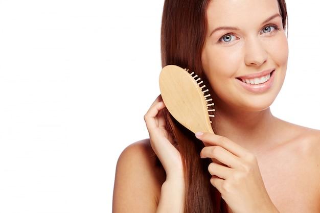 Mulher de sorriso que escova seu cabelo saudável