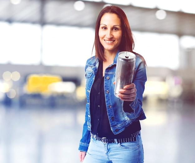 Mulher de sorriso que oferece uma lata