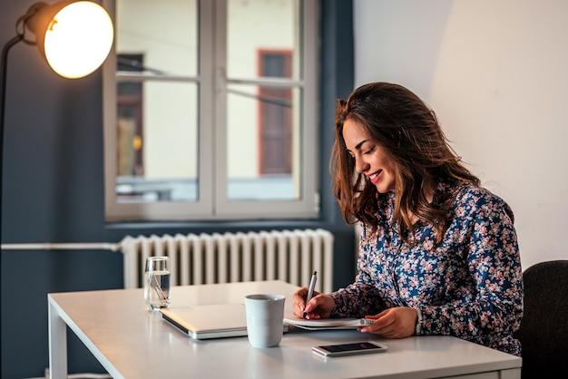 Mulher de sorriso que trabalha com papéis e portátil no escritório.