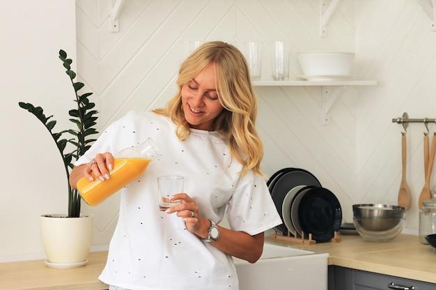 Mulher de sorriso que vai derramar o suco de laranja em um vidro na cozinha.