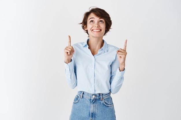 Mulher de sorte empolgada em uma camisa de colarinho azul, apontando e olhando para cima com um sorriso alegre, em pé na parede branca