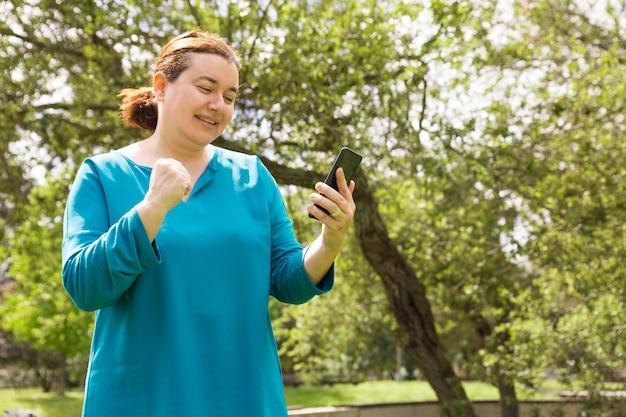 Mulher de sorte feliz com mensagem de leitura do telefone móvel