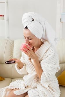 Mulher de spa em casa cheirando creme rosa