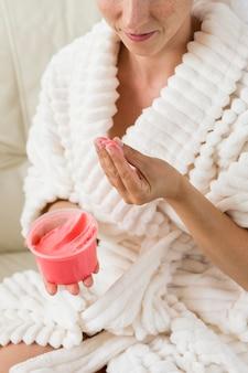 Mulher de spa em casa segurando um creme rosa