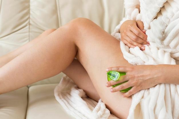 Mulher de spa em casa usando uma escova de esponja para massagem