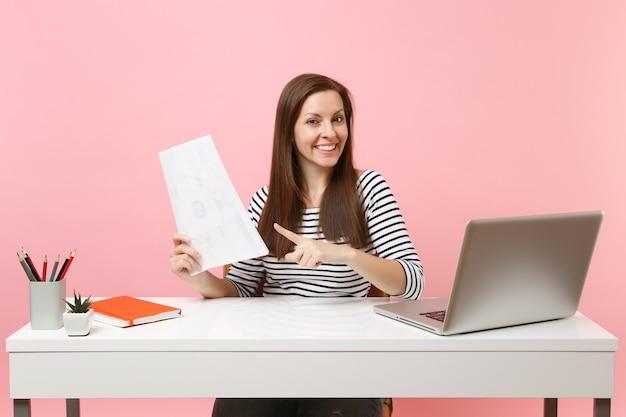 Mulher de sucesso apontando o dedo indicador em documentos em papel, trabalhando em um projeto enquanto está sentado no escritório com um laptop