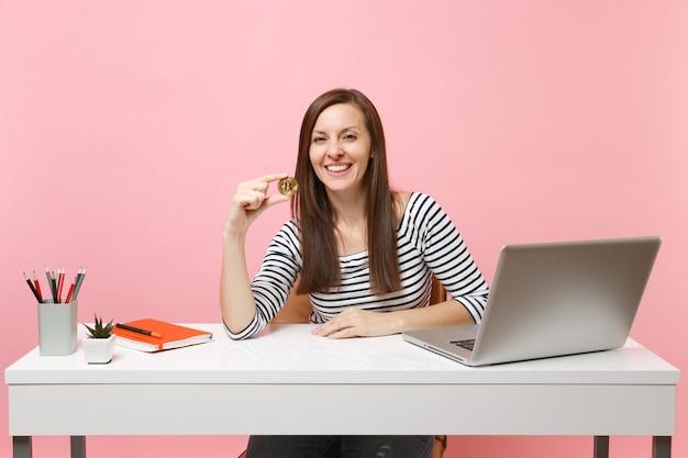 Mulher de sucesso segurando bitcoin, moeda de metal dourada, moeda do futuro, sentar no trabalho na mesa branca com o laptop do pc