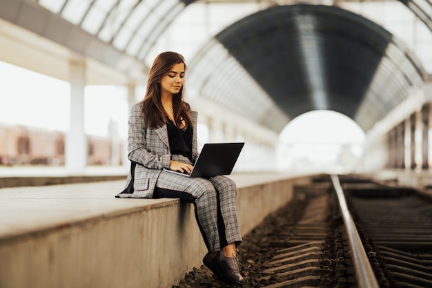 Mulher de sucesso usando laptop na estação de trem.