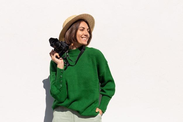 Mulher de suéter casual verde e chapéu ao ar livre na parede branca turista feliz positiva com câmera profissional