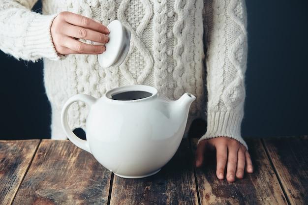 Mulher de suéter grosso de malha quente detém a tampa do grande bule de chá branco nas mãos, na mesa de madeira de grunge. vista frontal, anfas, sem rosto.