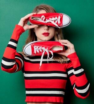 Mulher de suéter listrado com sapatos desportivos