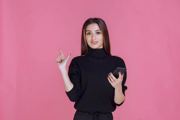 Mulher de suéter preto segurando um smartphone e apontando para ele.