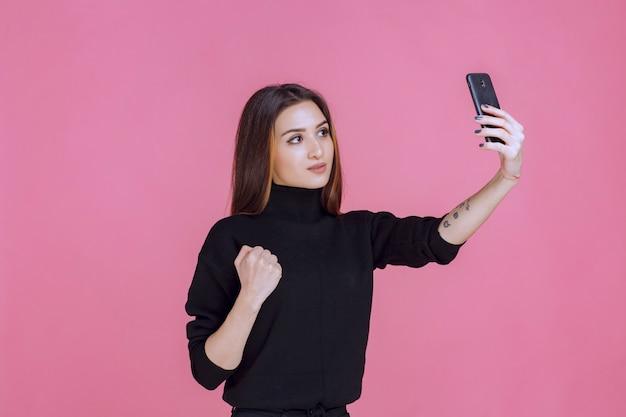 Mulher de suéter preto segurando um smartphone e tirando sua selfie.