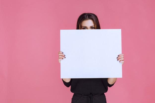 Mulher de suéter preto segurando uma placa quadrada de ideia.