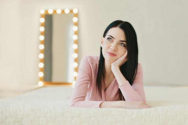 Mulher de suéter rosa deitada na cama, pensando