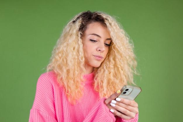 Mulher de suéter rosa verde segurando o telefone celular pensativa