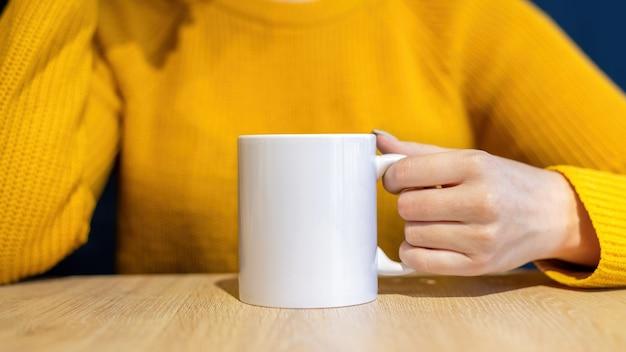 Mulher de suéter segurando uma xícara sobre uma mesa de madeira