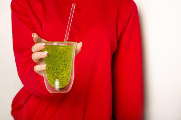 Mulher de suéter vermelho segurando um copo de suco de kiwi contra uma parede branca. espaço para texto