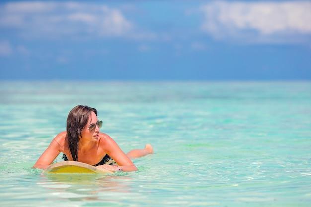 Mulher de surfista linda fitness surfando durante as férias de verão