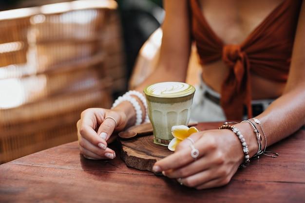 Mulher de sutiã marrom sentada em um café segurando um copo com leite matcha