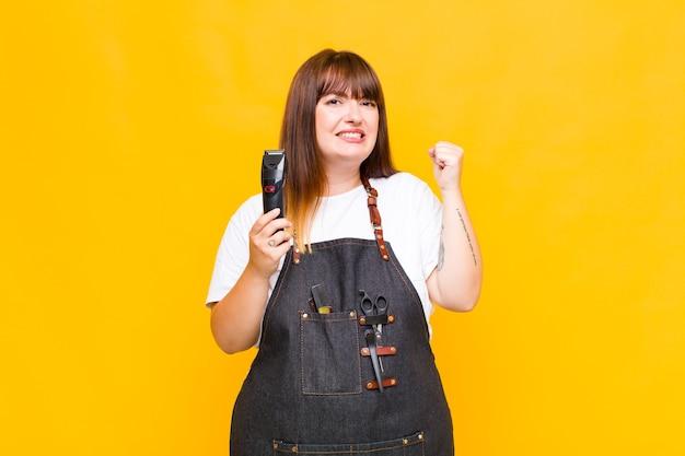 Mulher de tamanho grande gritando agressivamente com uma expressão de raiva ou com os punhos cerrados celebrando o sucesso