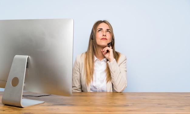 Mulher de telemarketing jovem de pé e pensando uma idéia