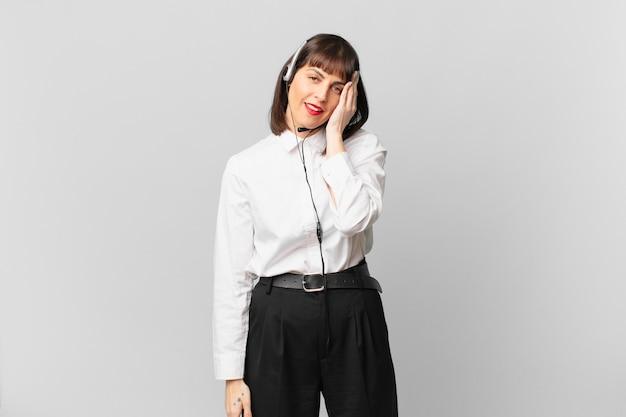 Mulher de telemarketing se sentindo entediada, frustrada e com sono depois de uma tarefa cansativa, enfadonha e tediosa, segurando o rosto com a mão