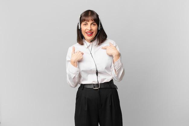 Mulher de telemarketing se sentindo feliz, surpresa e orgulhosa, apontando para si mesma com um olhar animado e surpreso