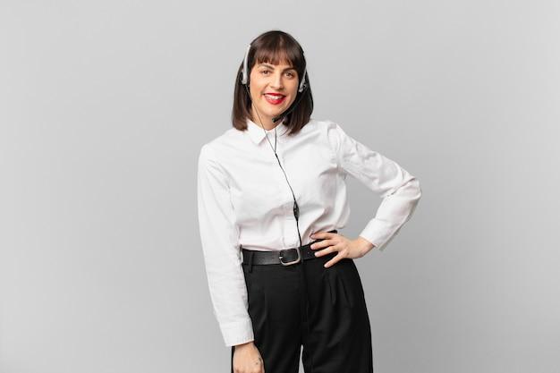 Mulher de telemarketing sorrindo feliz com a mão no quadril e com atitude confiante, positiva, orgulhosa e amigável