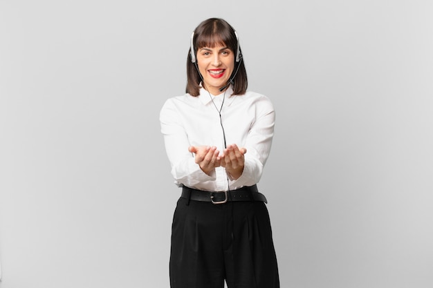 Mulher de telemarketing sorrindo feliz com um olhar amigável, confiante e positivo, oferecendo e mostrando um objeto ou conceito