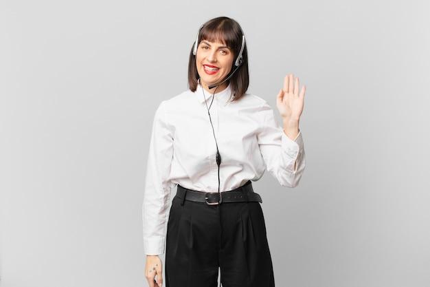Mulher de telemarketing sorrindo feliz e alegremente, acenando com a mão, dando as boas-vindas e cumprimentando você ou dizendo adeus