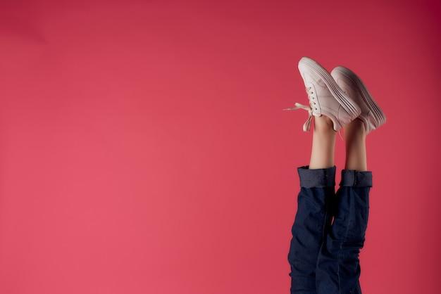 Mulher de tênis branco pernas rosa fundo posando