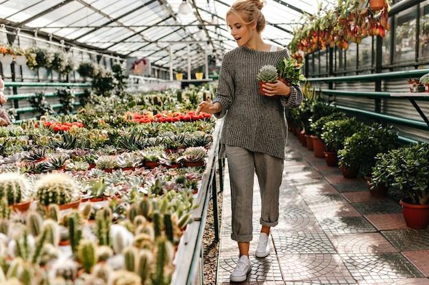 Mulher de tênis branco, roupa folgada cinza anda pela loja de plantas e segura cactos nas mãos.