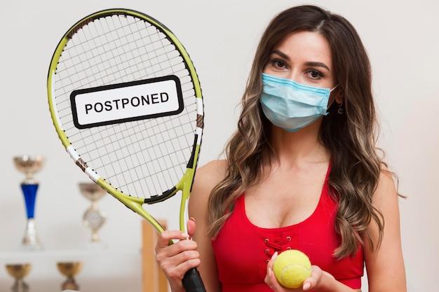 Mulher de tênis segurando um cartaz adiado na sua raquete