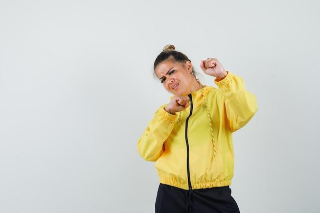 Mulher de terno esporte em pé em pose de boxeador e olhando poderosa, vista frontal.